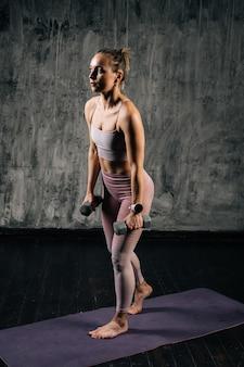 ダンベルを保持し、スクワットをしているスポーツウェアを身に着けている完璧な美しい体を持つ筋肉の若い運動女性の肖像画。濃い灰色の背景を持つスタジオでポーズをとる白人フィットネス女性。