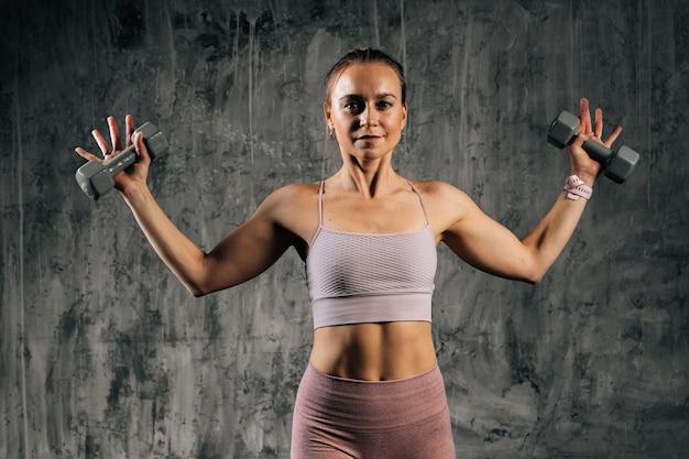 ダンベルを保持している腕を上げるスポーツウェアを身に着けている完璧な美しい体を持つ筋肉の若い運動女性の肖像画。濃い灰色の背景を持つスタジオでポーズをとる白人フィットネス女性。