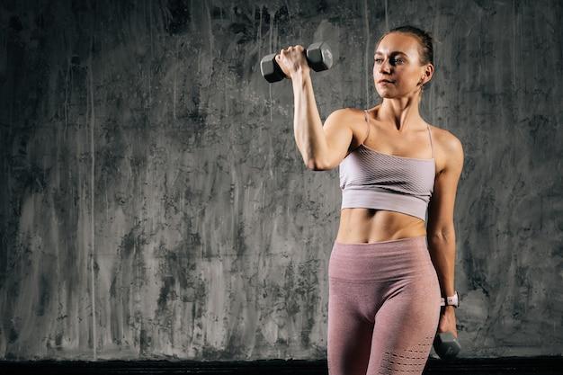 ダンベルで運動するスポーツウェアを身に着けている完璧な美しい体を持つ筋肉の若い運動女性の肖像画。濃い灰色の背景を持つスタジオでポーズをとる白人フィットネス女性。