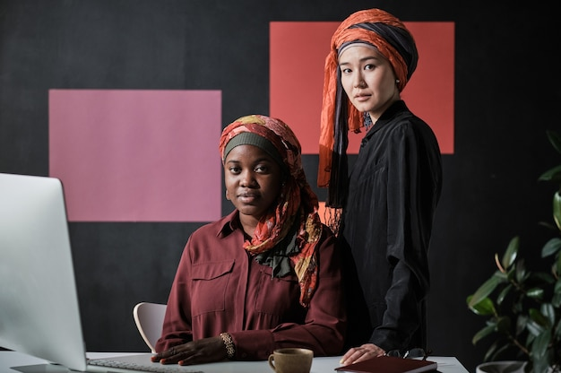 Портрет мусульманских деловых женщин, смотрящих в камеру, работая за столом на компьютере в офисе