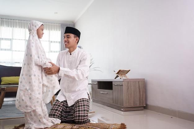 Портрет отца-мусульманина, учит дочь молиться дома
