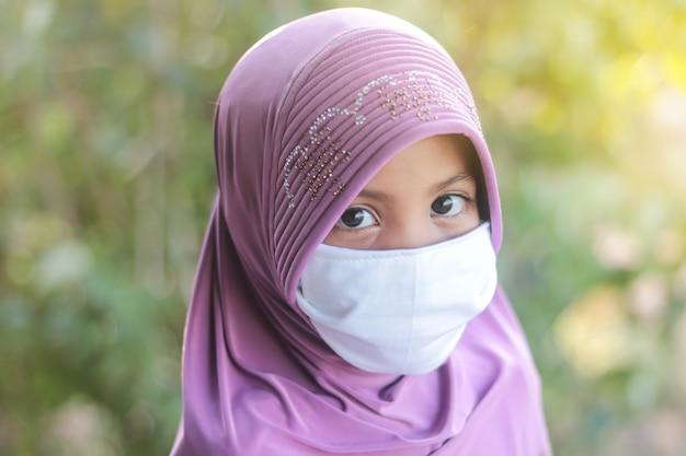 마스크를 쓰고 hijab와 이슬람 아이 여자의 초상화. covid-19 또는 coronavirus 개념.