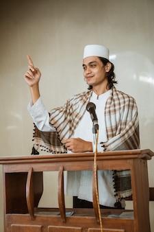 모스크에서기도 시간 동안 이슬람에 대해 공유하는 이슬람 남성 설교자의 초상화