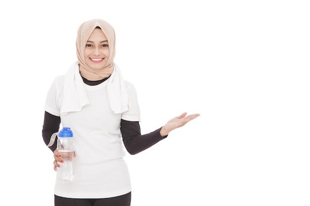 ミネラルウォーターのボトルを保持しているイスラム教徒のスポーティな女性の肖像画