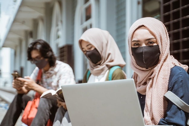 正面を見ている女子学生がマスクを身に着けているイスラム教徒の肖像画。バックグラウンドで忙しい友達と