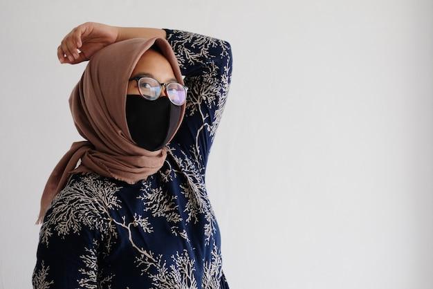 布製マスクを身に着けているイスラム教徒の女性の肖像画