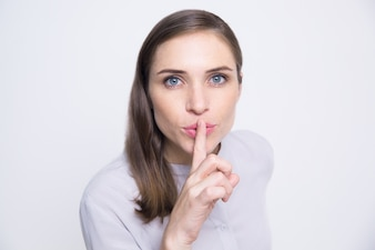 Portrait of mysterious woman holding finger on lip