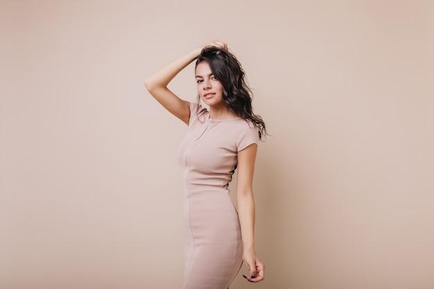 Портрет загадочной молодой женщины с волнистыми темными волосами. девушка-модель выглядит кокетливо