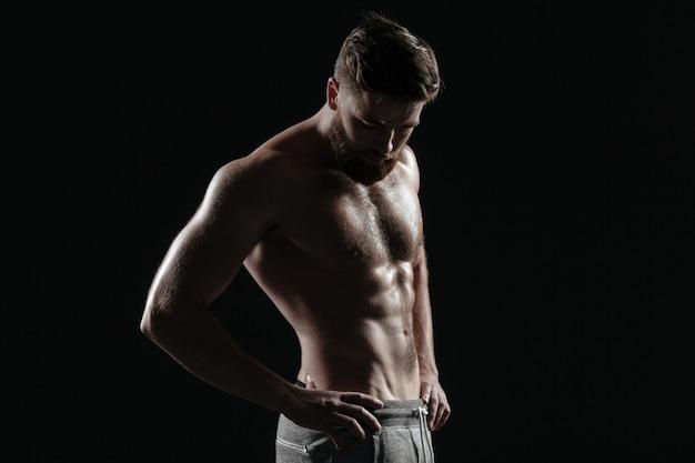 裸の運動選手の肖像画。孤立した暗い背景