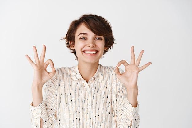 Портрет естественной счастливой женщины с короткой прической, показывающей хорошие жесты и улыбкой, одобряющей и нравящейся что-то, показывающей положительный отзыв, белая стена