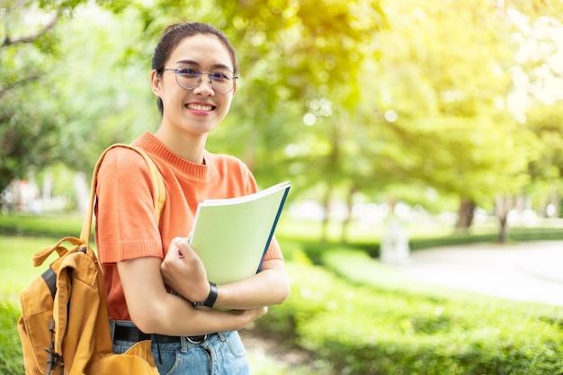 コピースペースと大学のキャンパスの屋外の緑豊かな公園で眼鏡をかけて幸せなオタクアジアの女性の女の子スマートティーンの肖像画