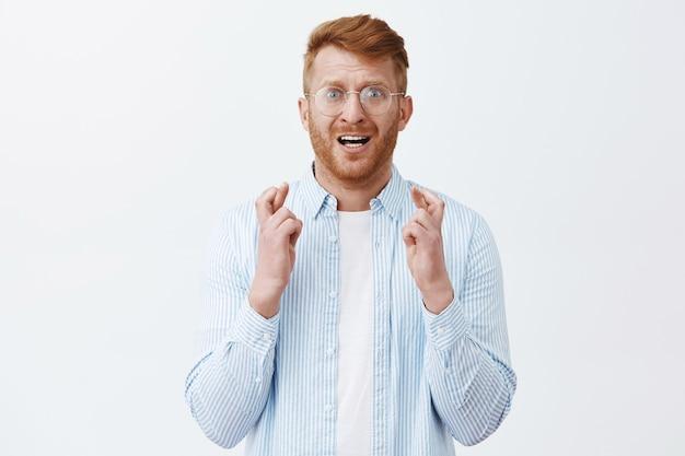 Портрет нервного и напряженного мужественного рыжеволосого мужчины с щетиной в прозрачных очках, скрещивающего пальцы и хмурящегося в тревожной надежде, что что-то произойдет