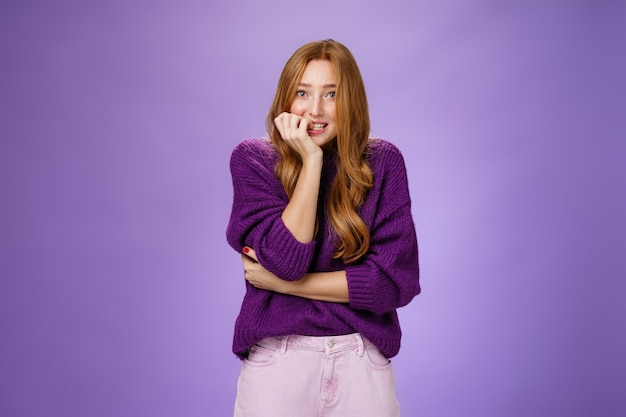 Портрет нервной небезопасной симпатичной рыжей девушки в фиолетовом свитере, кусающей ногти и сутулой, испуганной перед экзаменом или собеседованием, встревоженной и неуверенной на фиолетовом фоне.