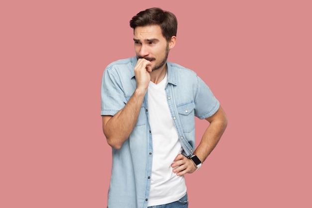Портрет нервного беспокойства красивый бородатый молодой человек в синей рубашке повседневного стиля стоял, глядя в сторону и кусая ногти. крытая студия выстрел, изолированные на розовом фоне.