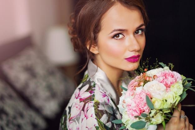 新婚の美しい女性の肖像画は花のバスローブで結婚式の日の準備を開始します