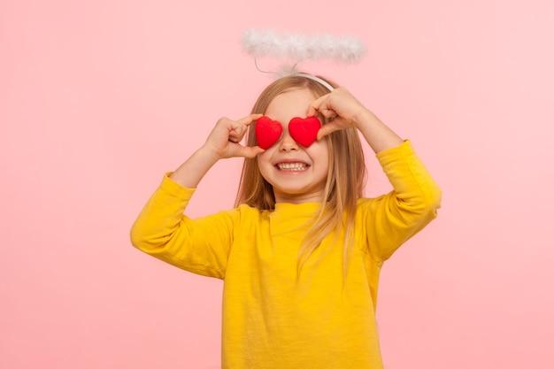 Портрет милой ангельской счастливой маленькой девочки с нимбом над головой, закрывающей глаза игрушечными сердечками и искренне улыбающейся, метафора взгляда, полного любви. закрытый студийный снимок изолирован на розовом фоне