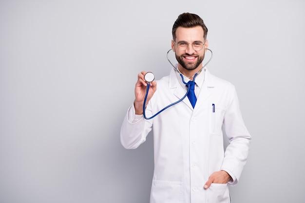 Портрет симпатичного привлекательного осторожного веселого веселого бородатого доктора, слушающего ваше дыхание, биение сердца