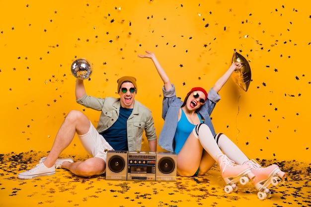 재미있는 디스코 레저를 즐기며 쉬고 있는 멋지고 쾌활한 커플 친구 우정의 초상화는 밝고 선명한 노란색 배경에서 분리되어 있습니다.