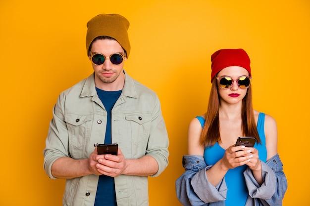 Портрет красивой привлекательной модной сосредоточенной серьезной пары, использующей цифровое устройство с приложением 5g в чате, изолированной на ярком ярком фоне яркого желтого цвета