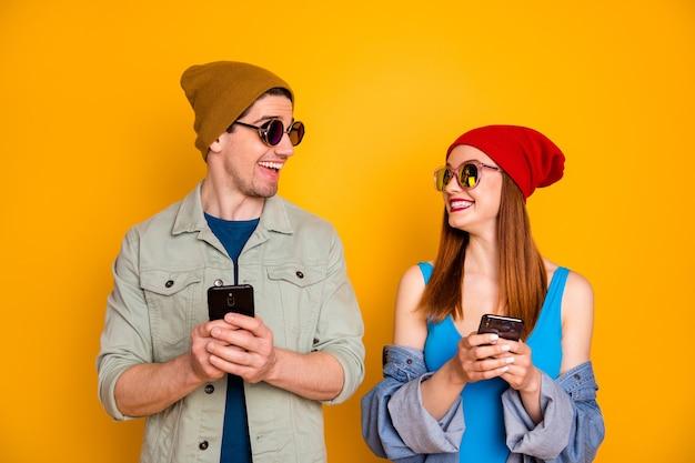 Портрет красивой привлекательной прекрасной довольно радостной веселой веселой пары, использующей приложение для устройства 5g, болтающих в свободное время в роуминге, изолированные на ярком ярком фоне яркого желтого цвета