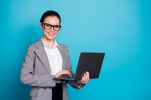 밝은 파란색 배경에서 원격으로 격리된 노트북을 들고 있는 멋지고 똑똑한 여성의 초상화