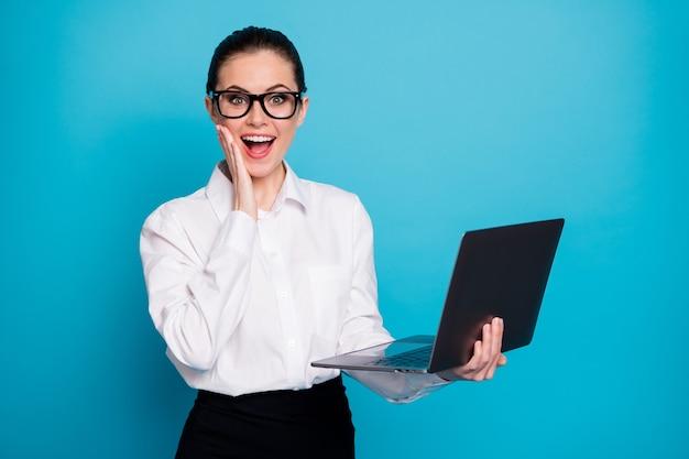 明るい青色の背景で隔離のラップトップeコマースを手に持っている素敵な魅力的なスタイリッシュで陽気な専門家の女の子の肖像画