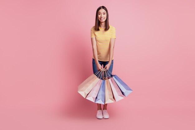 素敵な魅力的なスタイリッシュな女性の肖像画はピンクの背景に多くのパッケージファッションショップのコンセプトを保持します