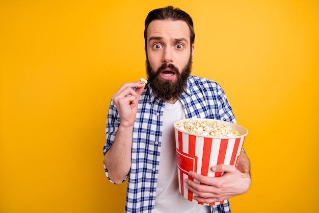 Портрет симпатичного привлекательного взволнованного испуганного зависимого бородатого парня в клетчатой рубашке, переедающего попкорн