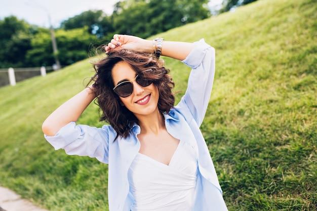 Портрет красивой девушки брюнетки с короткими волосами в солнцезащитных очках, улыбаясь в камеру в парке на фоне луга. она носит белую футболку, синюю рубашку.