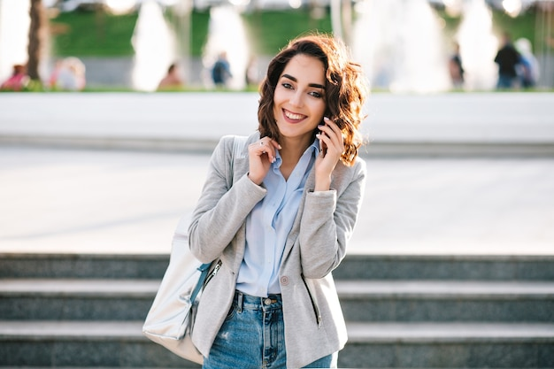 街を歩いて短い髪の素敵なブルネットの少女の肖像画。彼女はシャツ、ジーンズ、ジャケット、バッグを着ています。彼女は電話で話し、カメラに微笑んでいます。