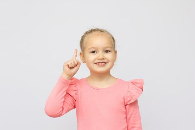 흰색 배경 위에 격리된 멋진 귀여운 사랑스러운 매력적인 사랑스러운 소녀의 쾌활하고 긍정적인 재미있는 포인트 손가락의 초상화