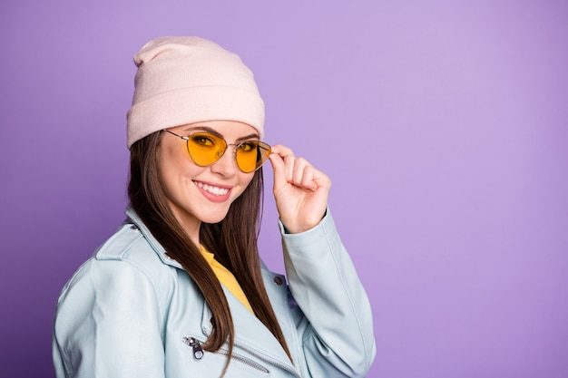 素敵な夢のようなコンテンツの若い女の子の肖像画は彼女のスペックに触れる良い歯を見せる笑顔は紫色の背景の上に分離されたカジュアルなスタイルの服を着る