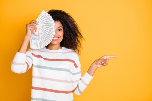 Портрет красивой девушки в свитере, скрывающей половину лица наличными, указывая в сторону