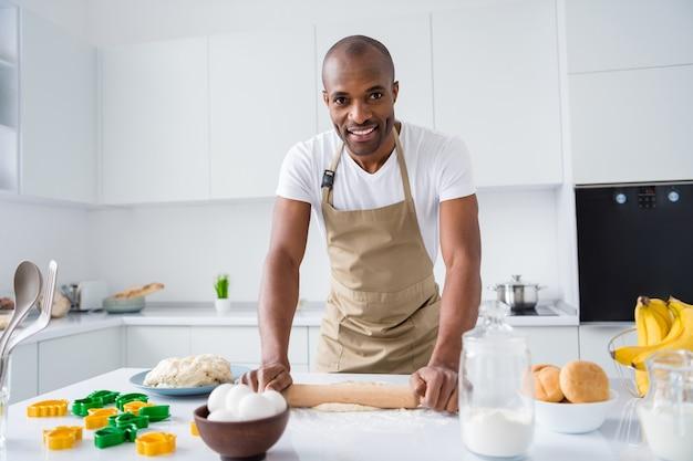 Портрет симпатичного парня-кондитера, делающего свежий хлебный пирог, замешивающего муку, учится