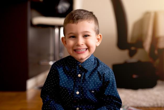 エレガントな青いシャツを着て素敵な小さな男の子の肖像画