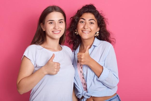 Портрет симпатичных привлекательных милых очаровательных жизнерадостных темноволосых дам, показывающих два больших пальца вверх, изолированные над ярким розовым пространством