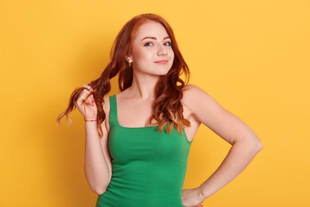カールの髪型を引っ張る見栄えの良い魅力的なかわいい女の子の肖像画