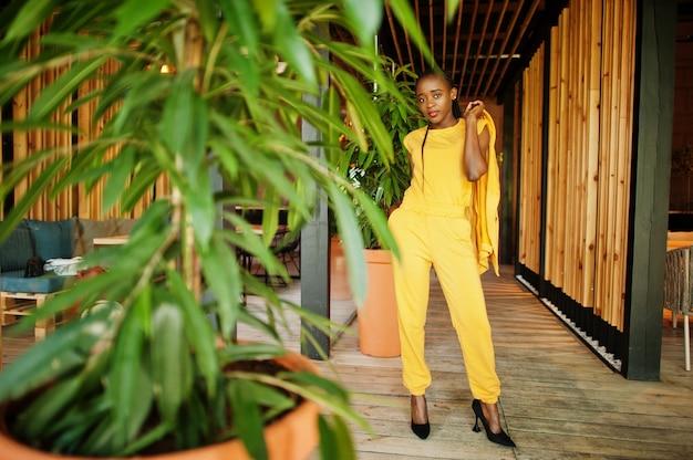 見栄えの良いファッショナブルな魅力的な素敵なコンテンツの肖像陽気な陽気なアフリカ系アメリカ人の女の子は、明るく鮮やかな輝きの鮮やかな黄色のジャケットや衣装を着ています。