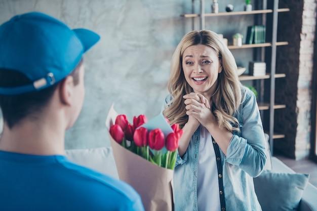 실내에 붉은 꽃을받는 좋은 사랑스러운 쾌활한 여자의 초상화