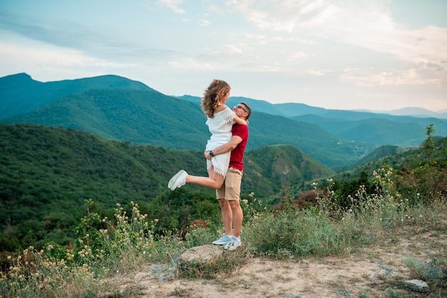 Портрет приятной милой милой пары, весело проводящей время на летних каникулах, счастливая пара обнимается в горах.