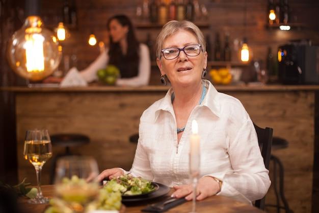 レストランで食事を楽しみながらカメラを見ている素敵なおばあさんの肖像画。白ワイン1杯。野菜のサラダ。