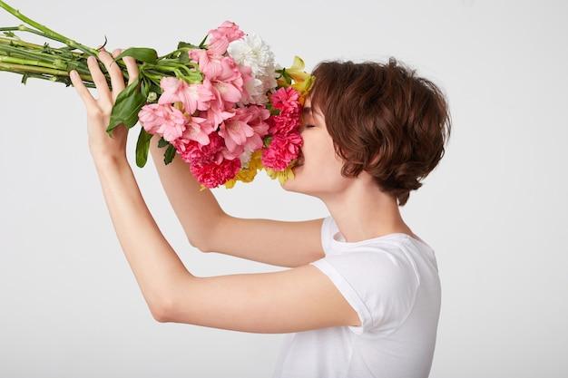 닫힌 된 눈으로 흰색 배경 위에 서있는 냄새를 즐기고, 화려한 꽃의 꽃다발을 들고 흰색 공백 t- 셔츠에 좋은 짧은 머리 여자의 초상화.