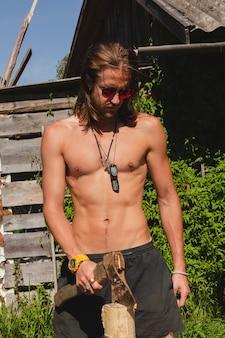 Портрет симпатичного парня топлес, раскалывающего бревна на заднем дворе в солнечный день.