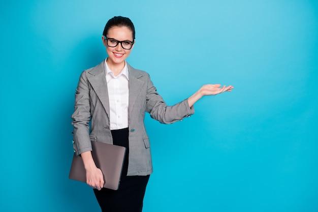 Портрет красивой модной веселой девушки с ноутбуком, держащей на ладони, копией пространства, место рекламы, изолированного ярко-синего цвета
