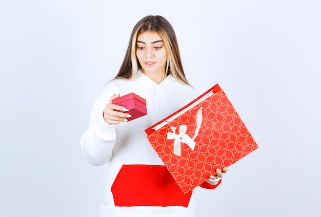 Портрет красивой женщины модели, стоящей и держащей сумку с маленькой коробкой