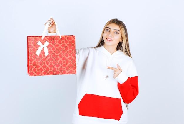 Портрет красивой женщины-модели, стоящей и указывающей на подарочный пакет