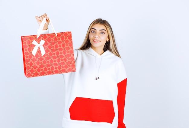 서 있고 선물 가방을 보여주는 좋은 여자 모델의 초상화