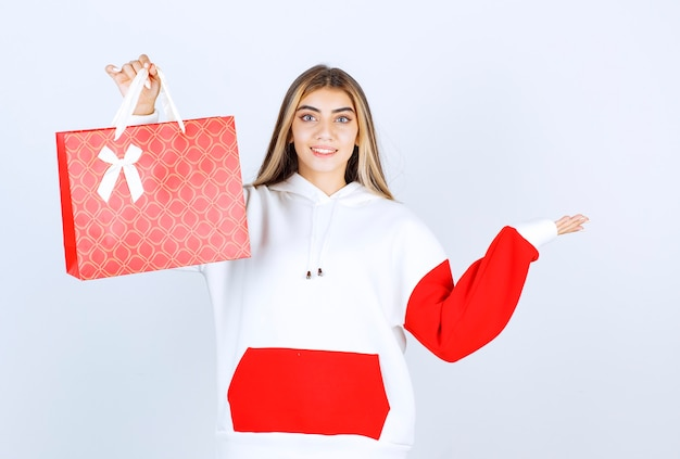 Портрет красивой женщины модели, стоящей и показывающей подарочный пакет