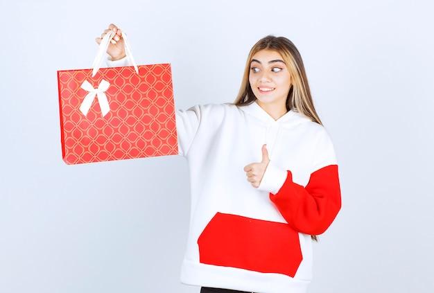 Портрет красивой женщины-модели, стоящей с подарочным пакетом и показывающей большой палец вверх