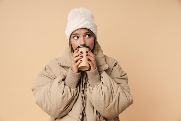Портрет красивой молодой женщины в зимнем пальто, пьющей кофе на вынос и смотрящей в сторону